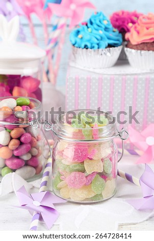 Multicolor candies in glass jars and cupcakes on color wooden background - stock photo