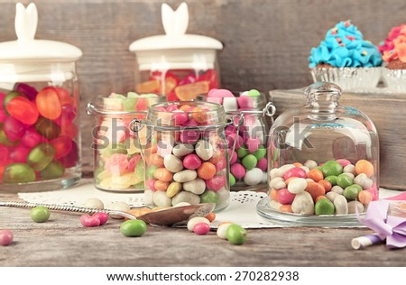 Multicolor candies in glass jars and cupcakes on wooden background - stock photo
