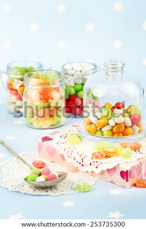 Multicolor candies in glass jars on colorful background - stock photo