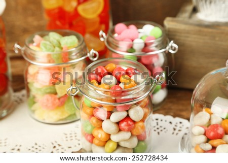 Multicolor candies in glass jars on wooden background - stock photo