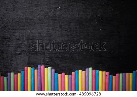 Multicolor chalk on desk for education background