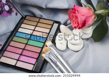 Multicolor eyeshadow and three cosmetic brushes, white stones and a rose  on the gray background - stock photo