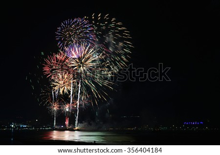 Multicolor fireworks night scene, closeup with pattaya cityscape sea beach view, Thailand. - stock photo