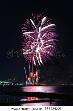 Multicolor fireworks night scene, closeup with pattaya cityscape sea beach view, Thailand.