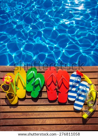 Multicolor flip-flops on wooden planks against blue water background. Summer family vacation concept - stock photo