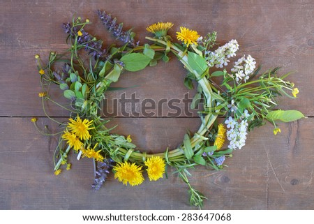 multicolor flower wreath on wood table - stock photo