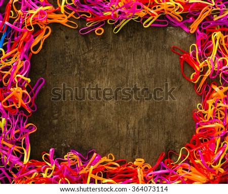 Multicolor loom loop rubber bands frame on the old wooden background - stock photo