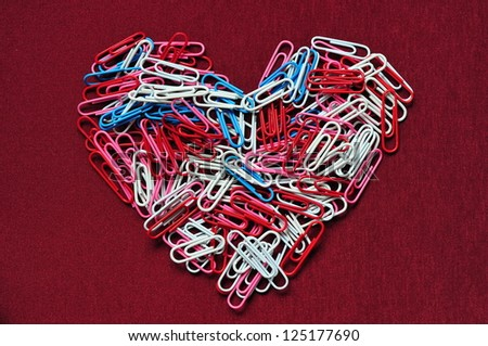 Multicolor paper clips arranged in heart shape - stock photo