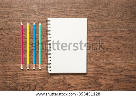 multicolor pencils with blank note book on wooden background, top view - stock photo