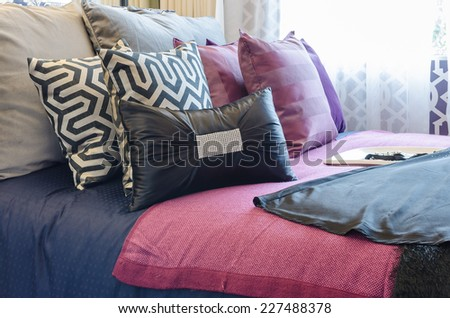multicolor pillows on bed in bedroom at home - stock photo