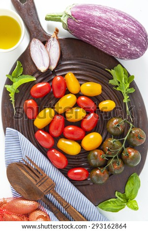 multicolor red and yellow cherry tomatoes on a cutting board for pizza - stock photo