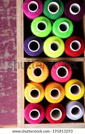 Multicolor sewing thread in wooden box, on wooden background, close-up