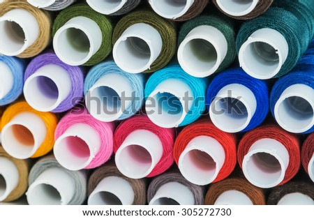 Multicolor sewing threads background. Focus blue thread, shallow depth of field - stock photo