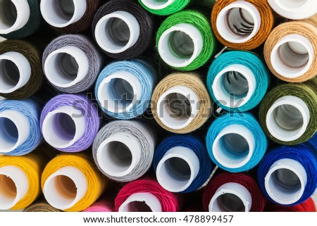 Multicolor sewing threads background. Focus blue thread, shallow depth of field
