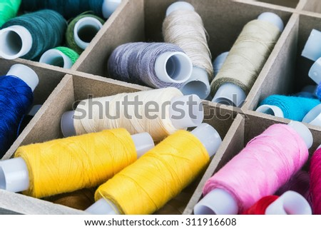 Multicolor sewing threads in a wooden box. focus on strings in the center of the frame - stock photo