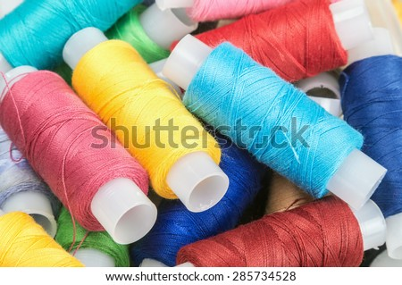 Multicolor sewing threads on background. focus on strings in the center of the frame - stock photo