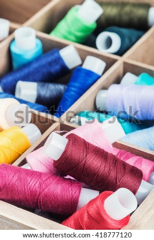 Multicolor sewing threads on background. focus on strings in the lower part of frame - stock photo