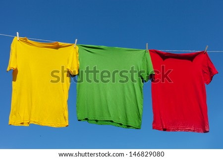 Multicolor shirts on clothesline in sunny day. - stock photo