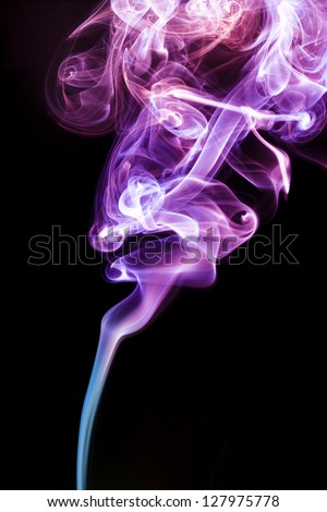 multicolor smoke rises up on a black background. - stock photo