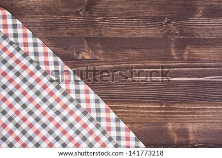 Multicolor tablecloth on vintage wooden table background - stock photo