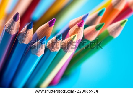 Multicolor wooden pencils against light blue background.