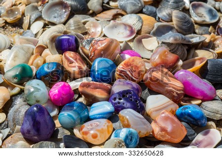 Multicolored agates with seashells on the beach - stock photo