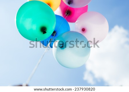 multicolored balloons on blue sky background - stock photo