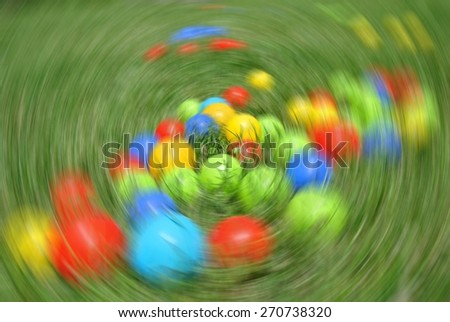 Multicolored balls - children's toys, on the green grass, on a sunny day, with radial blur. - stock photo