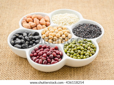 Multicolored beans in ceramics bowl on sack background.