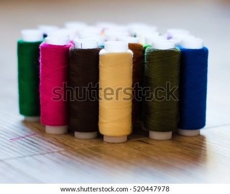 multicolored bobbin of thread on a wooden background