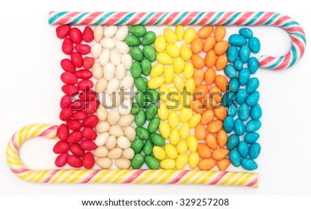 Multicolored bonbons and candy canes on white background - stock photo