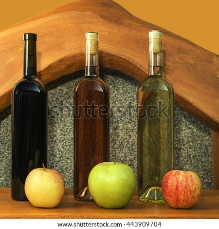 multicolored bottles of wine, in a composition with multicolored apples - stock photo