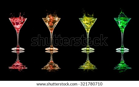 Multicolored Bright cocktails in glasses on black background with reflection - stock photo