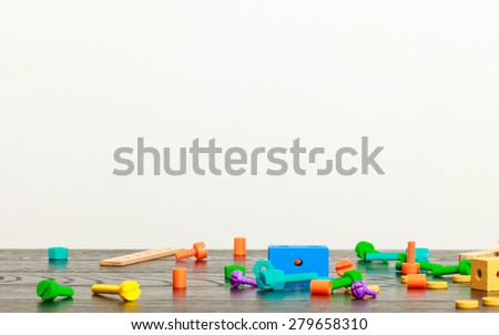 multicolored building blocks toy on wooden table empty interior white wall background