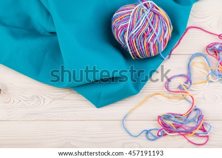 Multicolored bundle lie on blue piece of fabric on board table. Concept of hobby, knitting and enjoying calm pastime. Top view