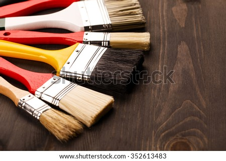 Multicolored clean paint brushes lying on wooden grey textured background, lying in a row