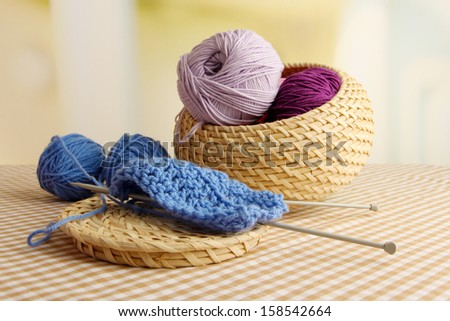 Multicolored clews in wicker basket with needles closeup - stock photo