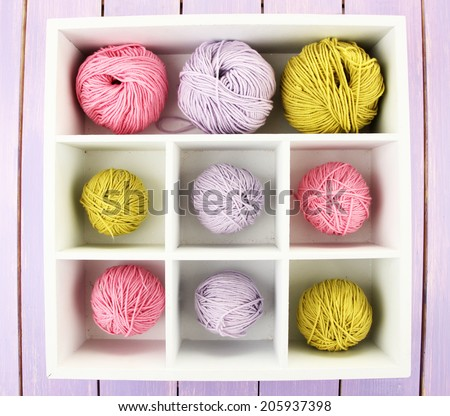 Multicolored clews in wooden box closeup - stock photo