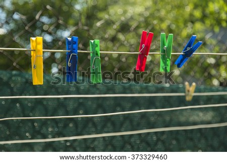 Multicolored clothespins on the clothesline. Colorful pegs on the green background - stock photo