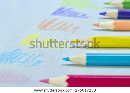 Multicolored crayons in a row, sketching on a paper  - stock photo