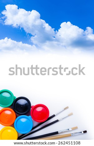 Multicolored drawing instruments (watercolor paints, paintbrush) for create imagination over sky background blank space, creativity concept. Top view - stock photo