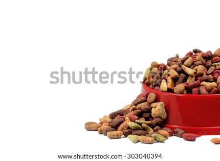 Multicolored dry cat or dog food in red bowl isolated on white background - stock photo