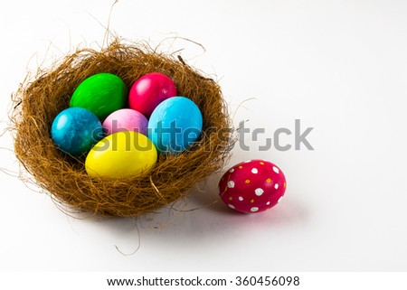 Multicolored Easter eggs in a nest and pink Easter egg with abstract design on white background. Easter background. Easter symbol. Top view with copy space - stock photo