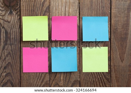 multicolored empty paper sticks for notes hanging on wooden noticeboard