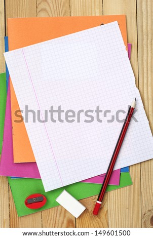 Multicolored exercise books, pencil, sharpener, eraser and clean sheet on table - stock photo