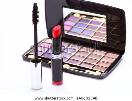 Multicolored eye shadows palette, red Lipstick and black mascara on a white background, selective focus - stock photo