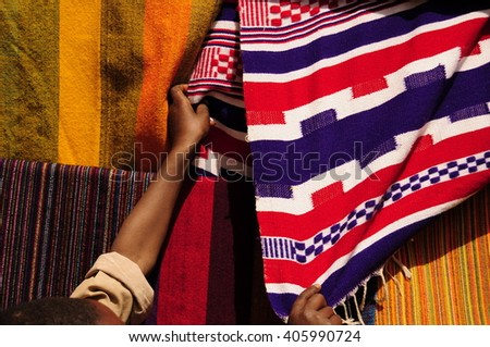 Multicolored fabrics and woman hands