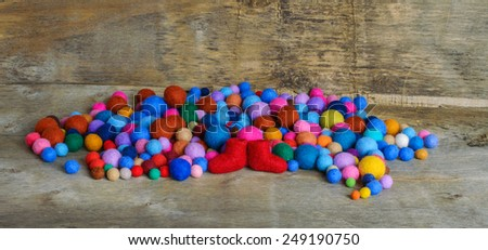 multicolored felted beads and red boots on the wooden background - stock photo