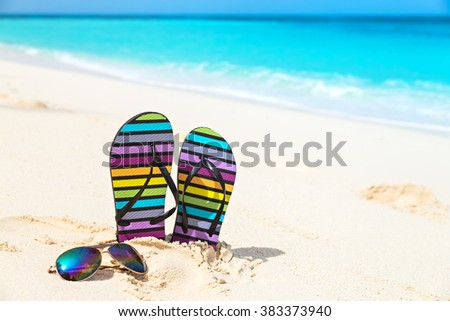 Multicolored flip-flops and sunglasses on a sunny beach.