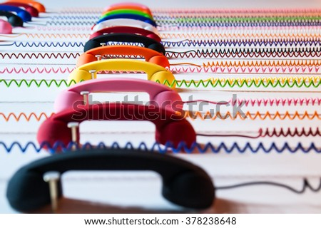 Multicolored handsets: yellow, blue, pink, green, red, white, orange. A spring wire spiral - stock photo